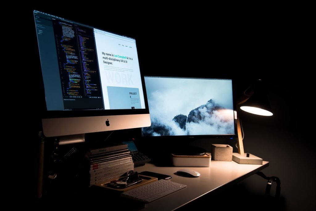 Workspace with two computers being lit by a desk light
