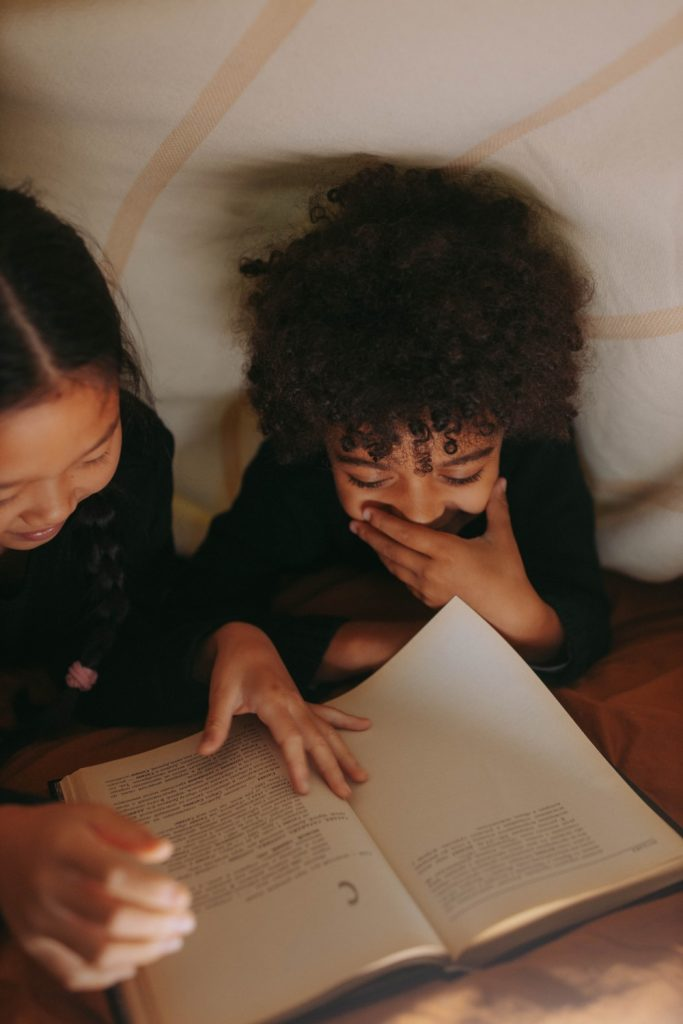 Two girls enjoying their story book in an area lit by the warm glow of VIO Brixton gold smart bulb