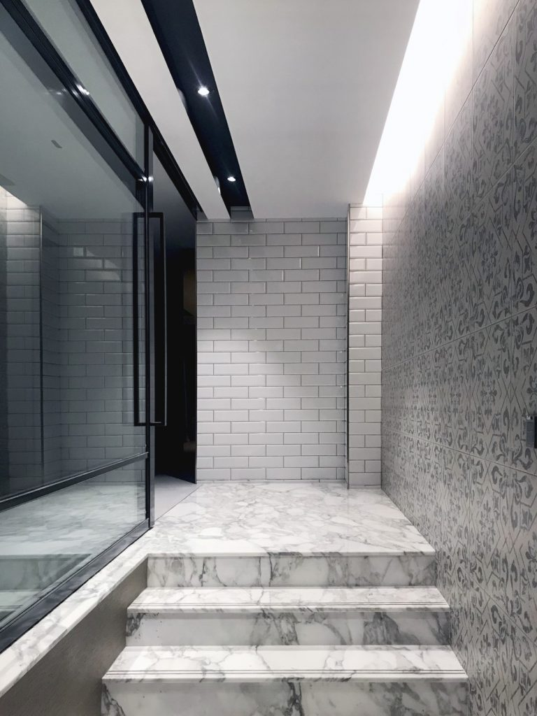Luxurious hallway with marble flooring lit by an LED strip and two spotlight
